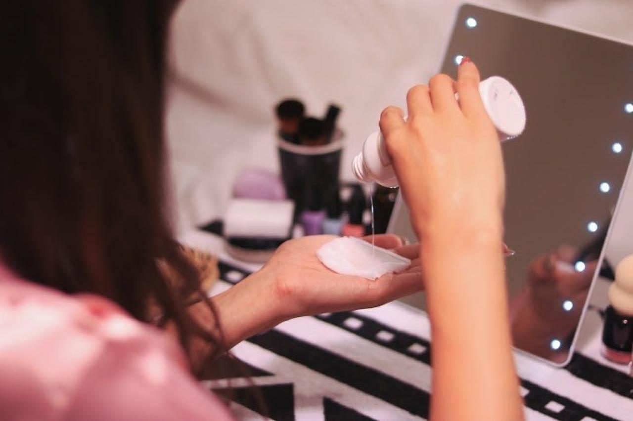 ドレッサーで化粧水をコットンにつけている女の子