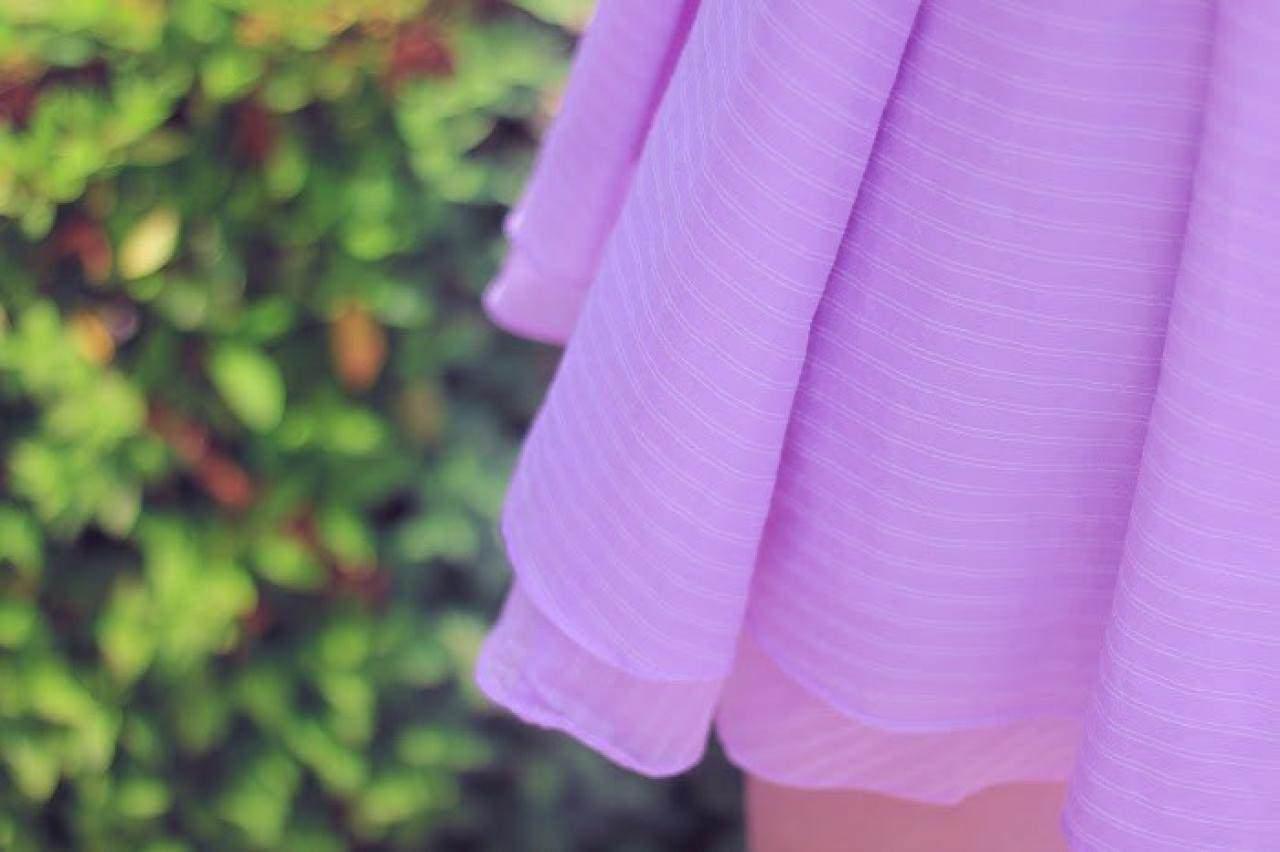 公園の生け垣の前で揺れるスカート