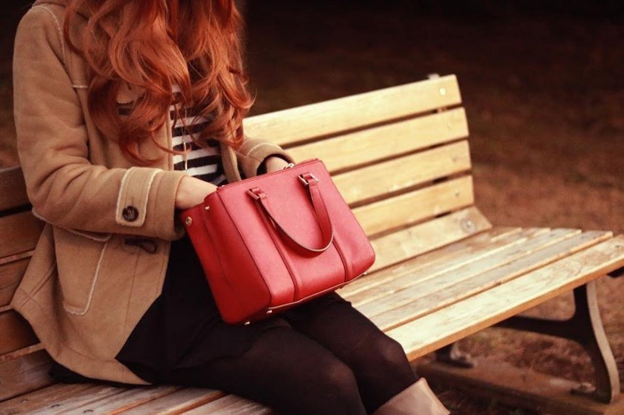 公園のベンチで赤いバッグをガサゴソする女の子