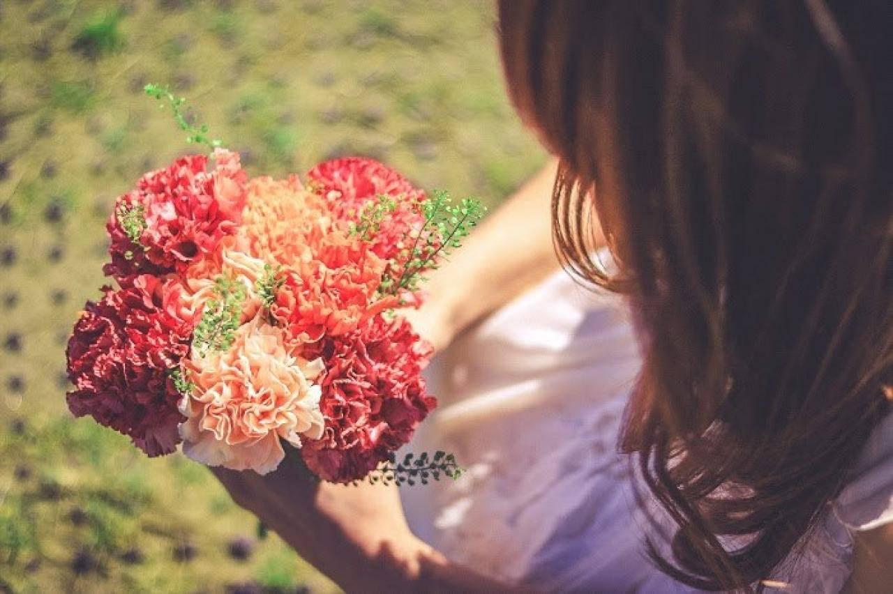 公園でしゃがんで花束をみつめる女の子