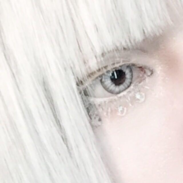 自まつ毛に下地をしっかり塗った後金の付けまつげをつけ、指で摘んで馴染ませる。 馴染んだらマスカラ下地をもう一度塗り白いアイシャドーを乗せる。 下まつげも同様に白くする。 ポイントは目を大きく見せようと欲張らずに、自まつ毛のように見せるためギリギリ目の極に付ける。