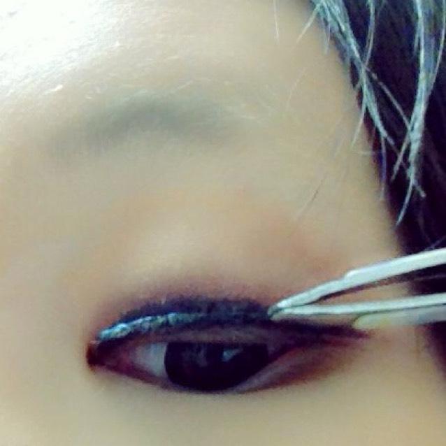 つけまを目尻から目頭に向かってつけます 目尻は2mmほど浮かし、黒目のところは3mm浮かし、目頭はなるべく浮かせずにつけます。目尻→目頭に向かうときに軽く引っ張りながらつけるのがポイントです