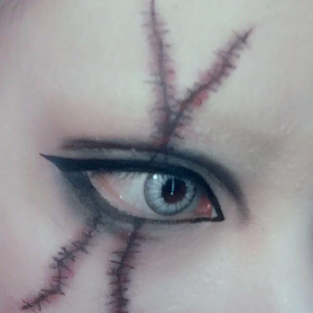 反対の目は黒シャドーをメインに。 アイラインも太めに囲ってダブルラインも太く濃くぼかす。 アイライナーで傷と縫い跡を描き黒と赤のシャドーでぼかす。 この工程ができたら上下に沢山付けまつ毛を付ける。