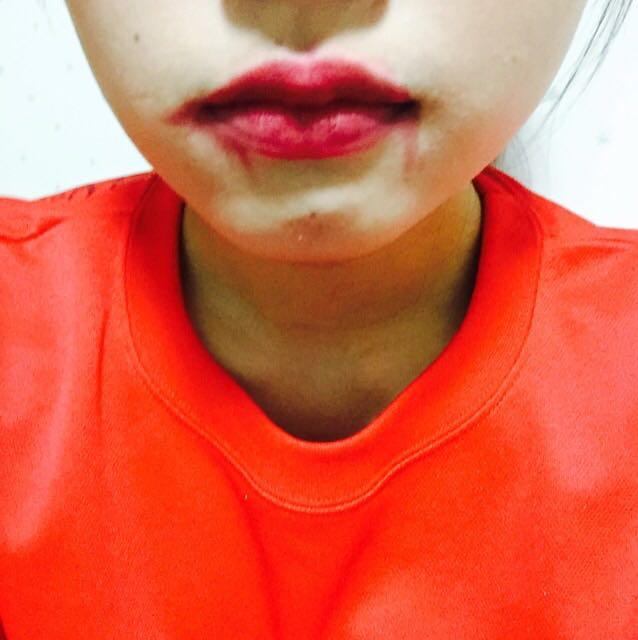 黒のアイシャドウを唇の端から内側へぽんぽんとする。 塗った赤リップを適当に血っぽくなるようにのばす