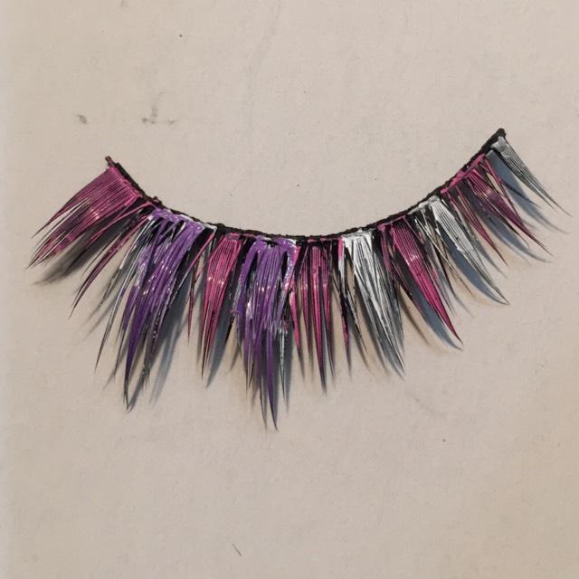 つけまを裏返し、ピンクと紫のポスカで交互に毛束に色を塗る。 紫色は黒の上では発色しにくいので一度白のポスカで塗って乾かしてから塗ると明るく発色します。