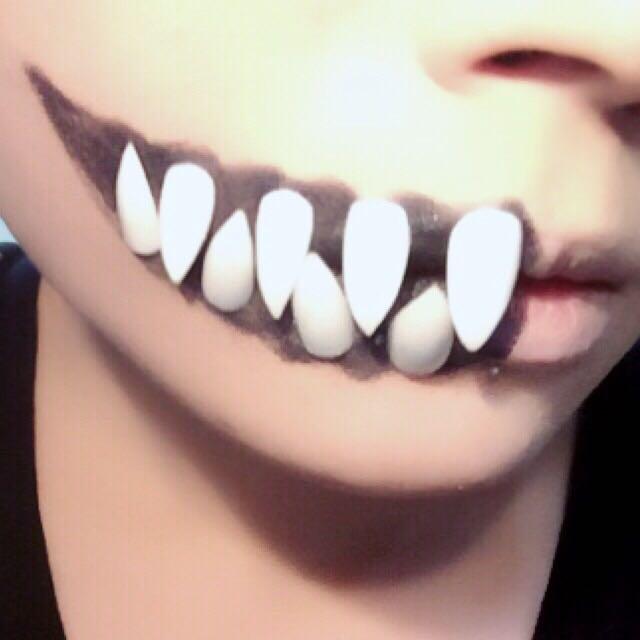 口の半分側を黒のシャドーで口裂け風に適当に塗りつぶし、作った牙の裏側にアイプチの糊をたっぷり付けて半乾きのタイミングで上下交互に並べていく。 ネイルチップのカーブで隙間があると付きにくいので糊はたっぷり。