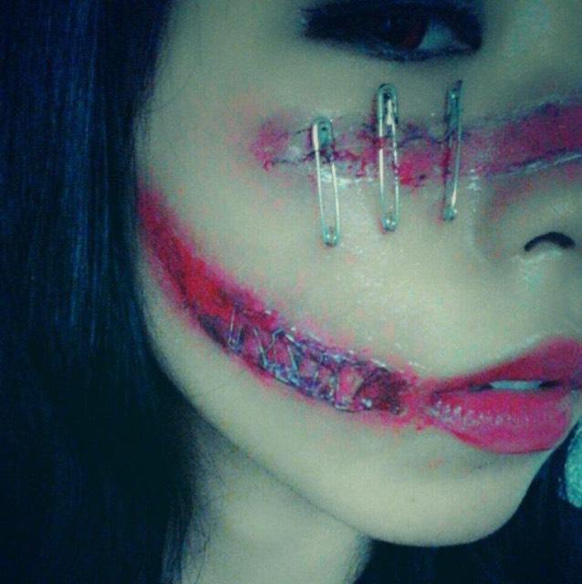 ティッシュで傷の型を取ってアイプチで貼り付けて安全ピンをテイッシュに刺してます 口元は同じようにテイッシュで型を取ってホッチキスの針を食い込ませてます。傷の中身の部分は赤リップや黒シャドーでそれっぽく。