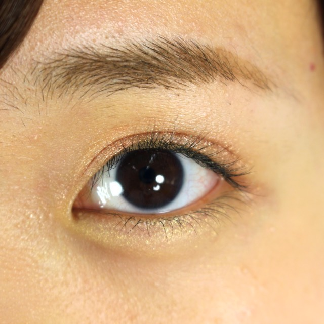 アイシャドウを重ねる  上瞼にオレンジ系のアイシャドウを重ねて塗る。(フォトレディ アイアートリッド+ライン+ラッシュ 06ピーチプリズム)