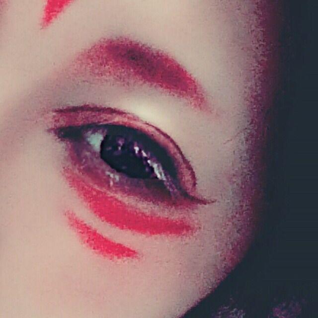 3.アイライナーでアイラインをひいていきます。しゅっと猫目ラインで跳ね上げます。 それから切開ラインを足します。 目の下の部分には二重幅や眉毛に使ったものよりも黒に近い濃い赤の口紅を筆にとって目頭から目尻まで塗って、目尻の部分は最後丸くなるように塗ります。