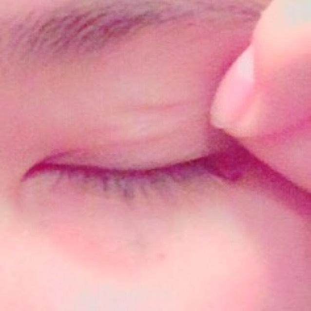 目頭から絆創膏を貼り、目尻まで食い込ませるようにひっぱります