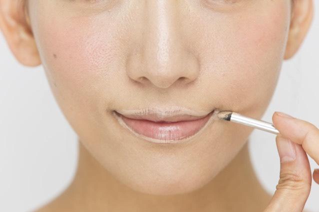 「コンシーラー」をチップに取り、唇の輪郭上にのせる。指の腹でポンポンとなじませ、唇の輪郭を消す。