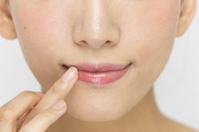 「赤リップ」を指に取り、唇全体にのせる。こすらず、ポンポンとスタンプを押すようになじませて。