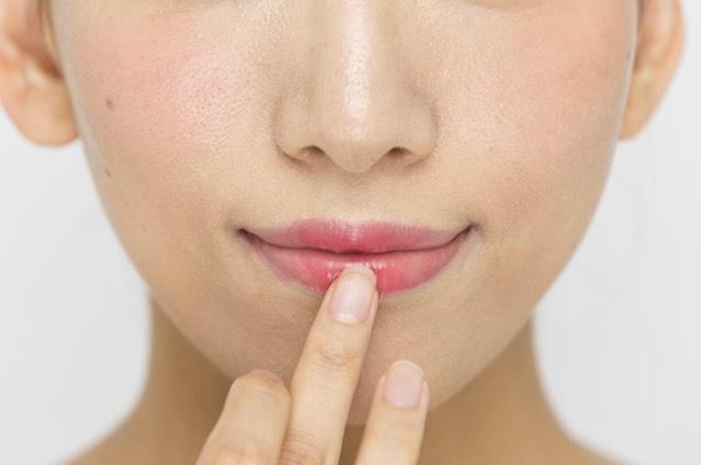 同じ赤リップをもう1度指に取り、唇の中央部分のみに重ねづけ。立体感を演出する。