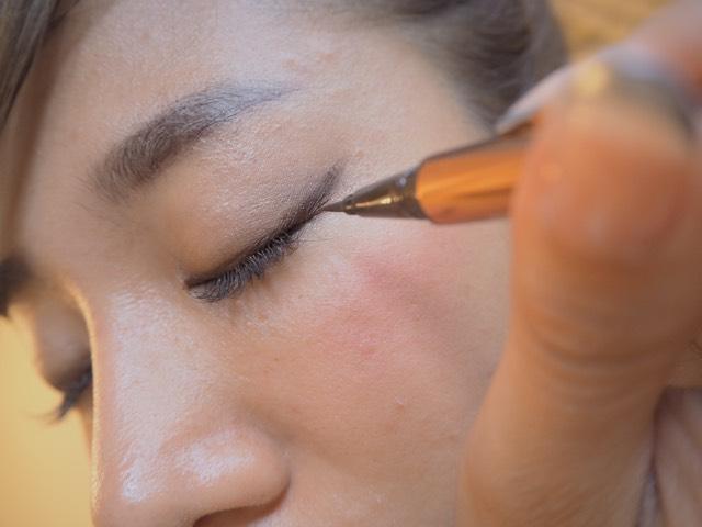 最後にブラウンのラブライナーのリキッドで、オーバー気味にラインを描きます。目尻に行くときにすこし筆のコシを使って太くするのがコツ