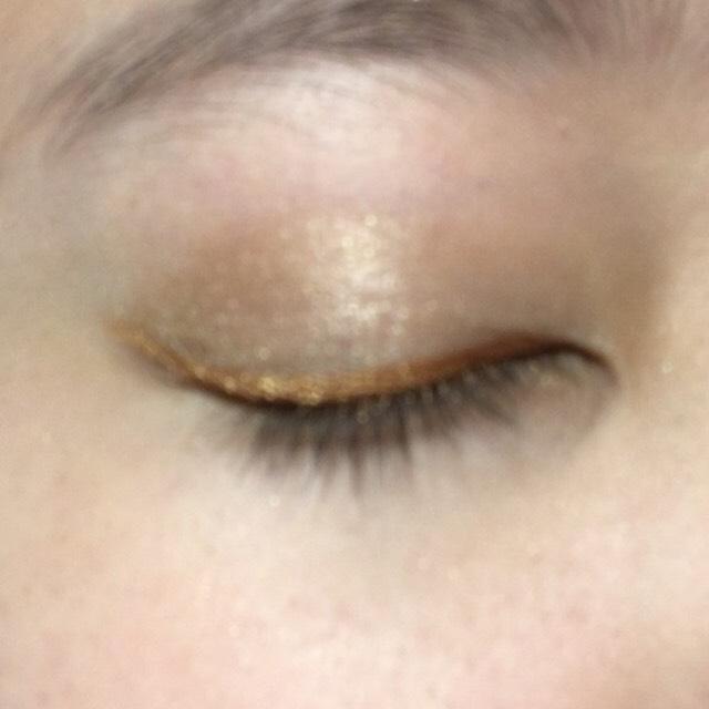 アイライナー用の筆を水で濡らし、オレンジのシャドウを、目の際にアイライナーを引くようにして、塗る。