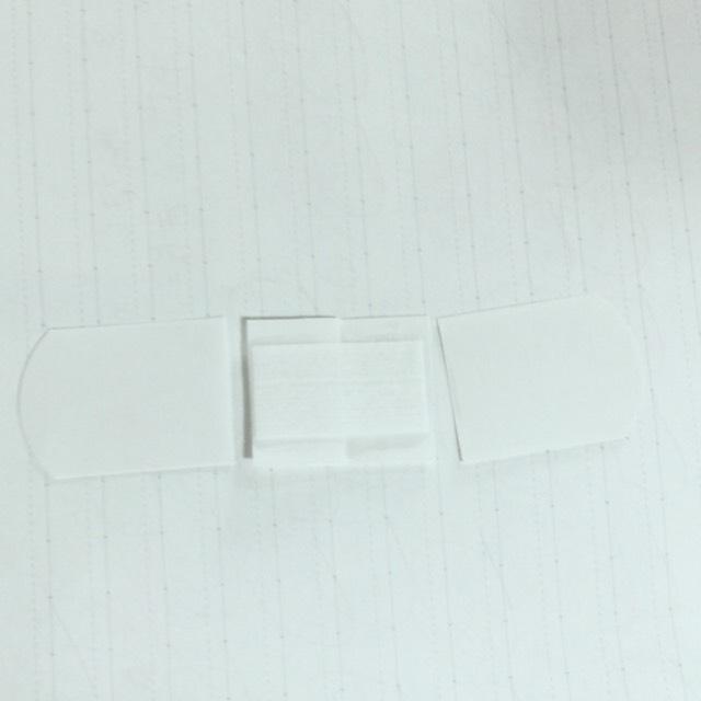 次に絆創膏を袋から出し、ハサミでこのようにカットします