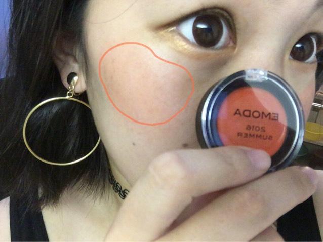 次にEMODAのリップ&チークを線で描いてるところあたりにつけてのばし、ほんわかとオレンジ色がわかる程度にします。