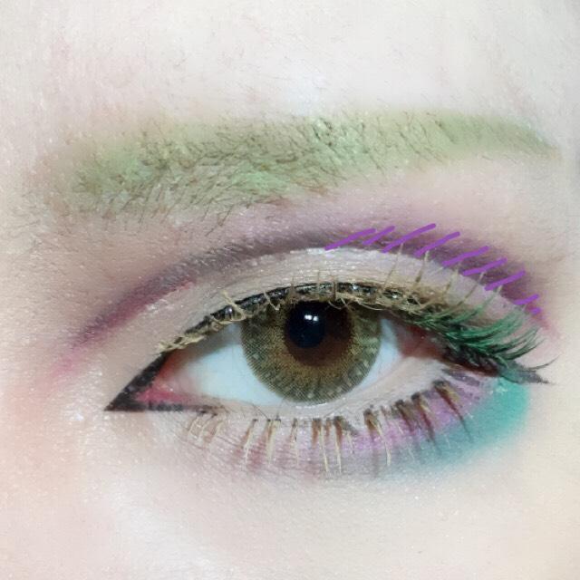 つけまを付けて眉コンシーラーで明るいまつげにした後お好きなカラーシャドーで遊びます。今回は紫×緑でアクセントを付けました。 シャドーに合わせて目尻にグリーンマスカラ。