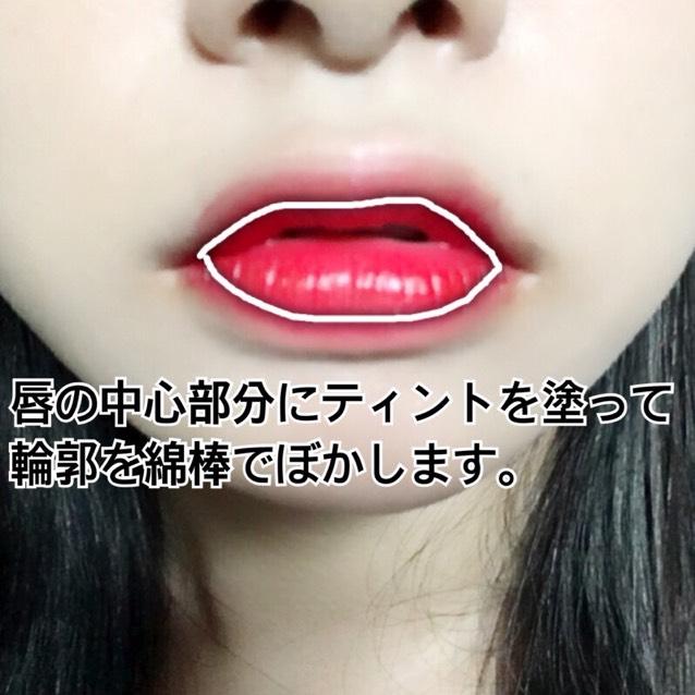 唇の中心部分にティントを塗って輪郭を綿棒でぼかします。
