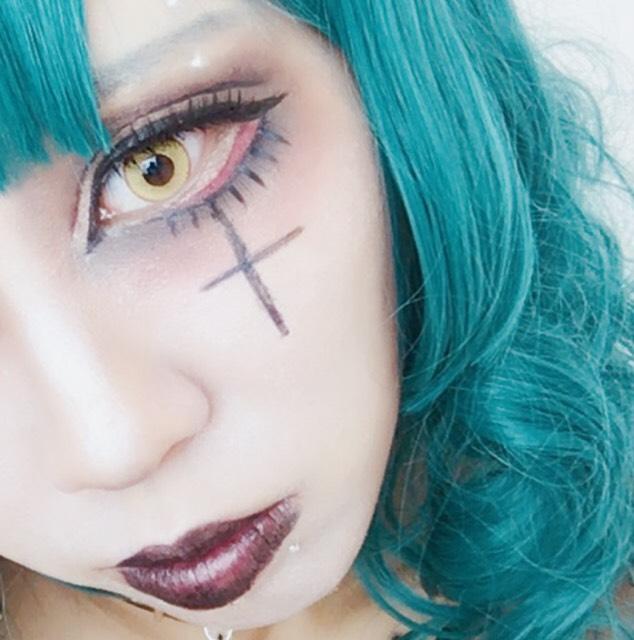 目の下に十字架をアイライナーでかきます。 デコレーション用のシルバーパーツをフェイクピアスの代わりにして眉、口、鎖骨に貼り付けます。