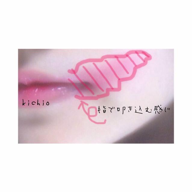 唇に赤リップとリップジャムを塗ったら、 片方の口角からはみ出すように広範囲に赤リップを薄く指で叩き込む