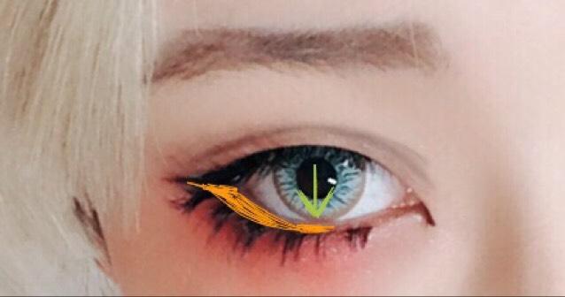目の下のオレンジの部分を黒のシャドーで塗り潰します。 黒目の部分より目頭近くは塗らないのがお勧めです。女の子らしくするなら塗っても○  男装時はつけまはつけた後にビューラーで下に下げた方が自然に見えます。