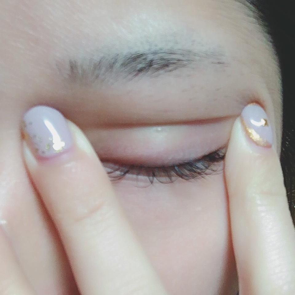 目を瞑った状態で写真のように瞼を引っ張ってできた線のところにつけまのりを塗っていきます(これを2回ほど繰り返します)
