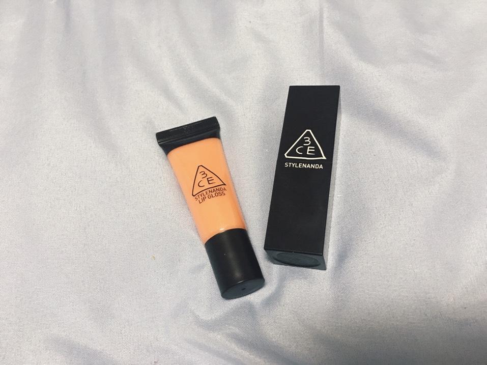 リップは3CEのリップを使います。 まず、オレンジのマットリップ(3CE#407 CASHMERE ORANGE)を唇の内側に塗り、指で唇全体がうっすらオレンジ色になるようにぼかします。そして、3CEのグロス(#BABY PUNCH)を重ねます。