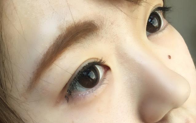 つけまつげにのりをつけてのりが半透明になったら、黒目上、目頭、目尻の順に抑えてつけます。 目元は少しはみでますがタレ目に見せたかったのでこのままつけました。
