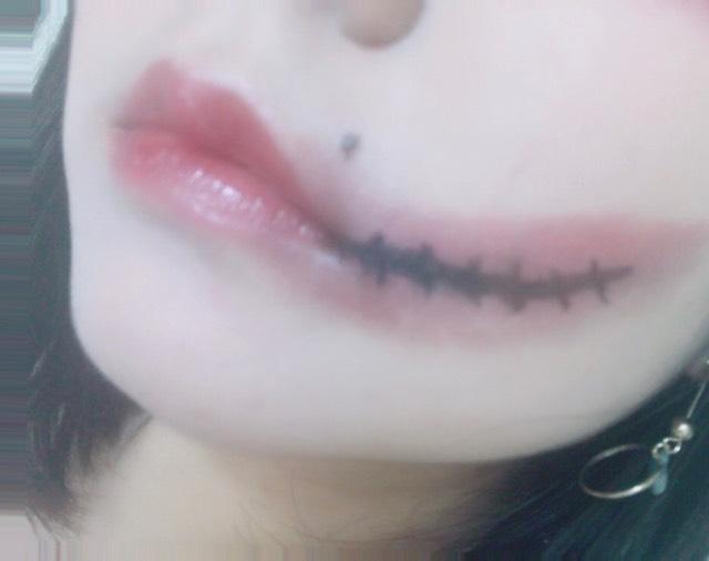 口や頬の色については、赤リップを塗りたくり、その上から紫のシャドウを指でのせる! 指に着いた分をアチコチに広げてく!