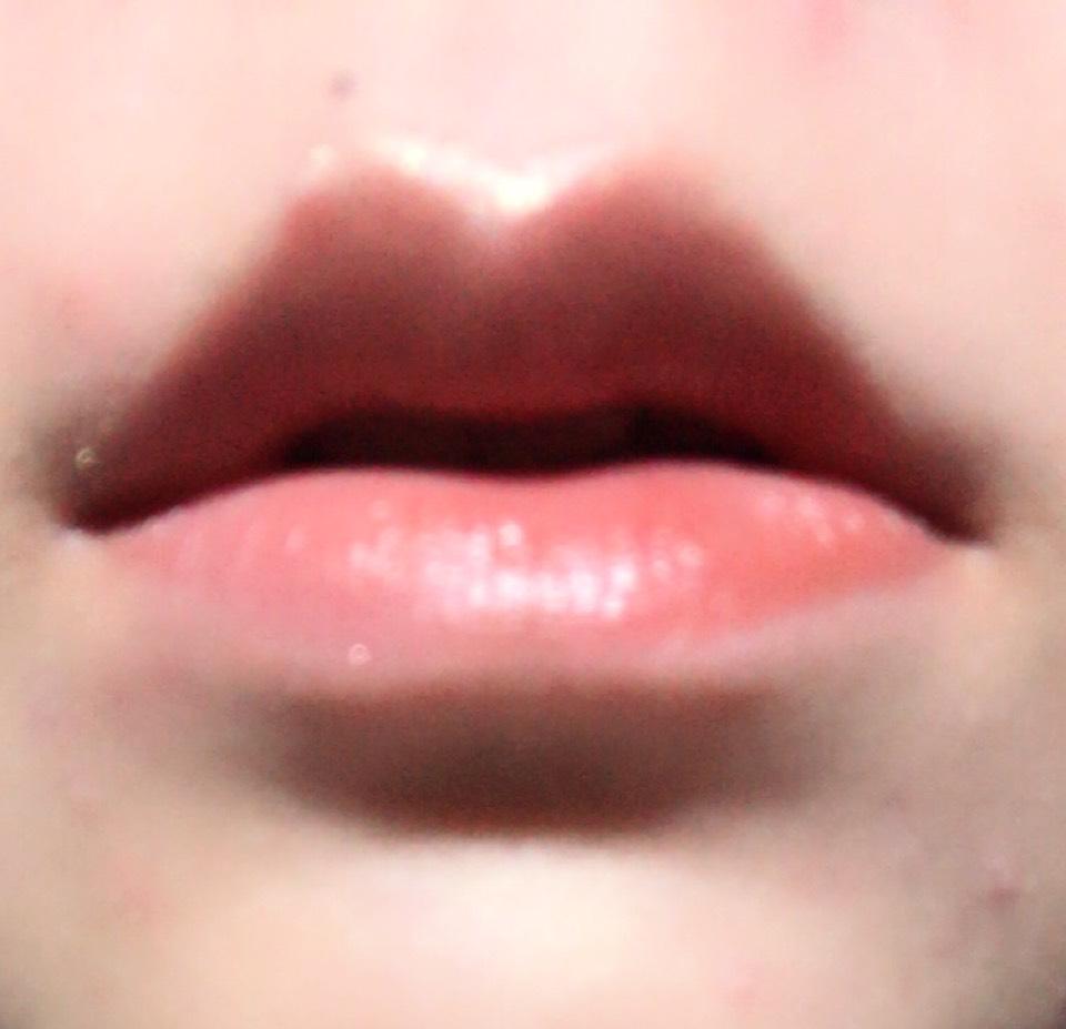 上唇の輪郭に沿ってハイライターペンシルでラインを引き、レンガカラーのリップを塗ります。