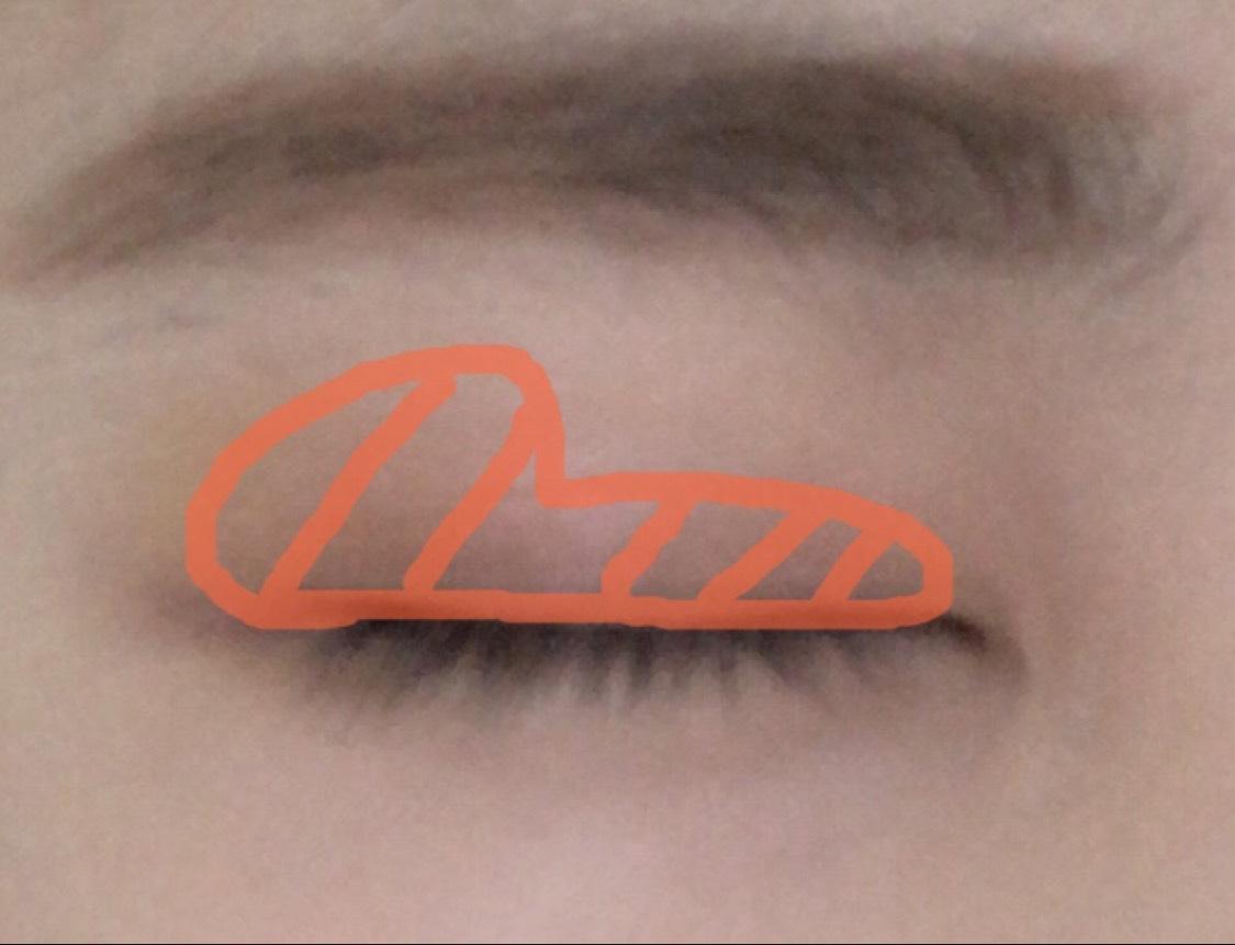 濃いオレンジで囲っている、ボルドーカラーのシャドウを目尻多めに塗ります。